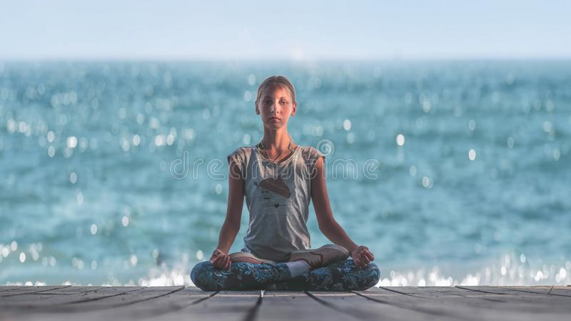Baby girl in Lotus pose on the background of the sea stock photos