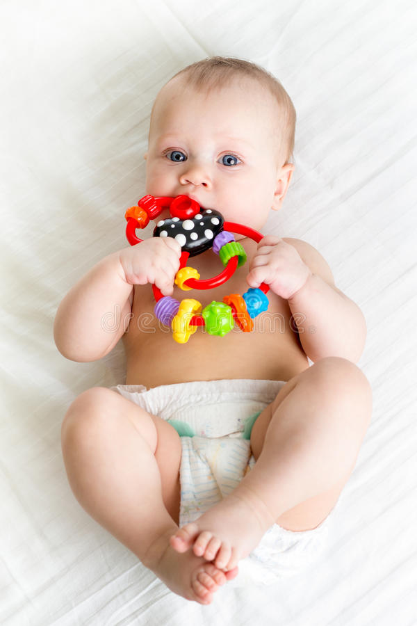 Baby girl lying on back weared diaper with teethers royalty free stock photo