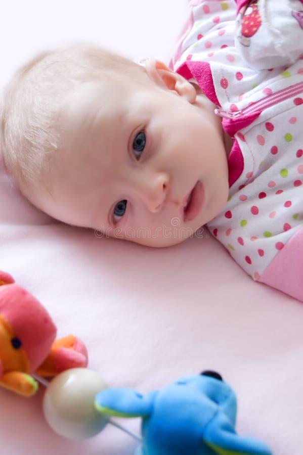 Baby girl lying on bed stock photos