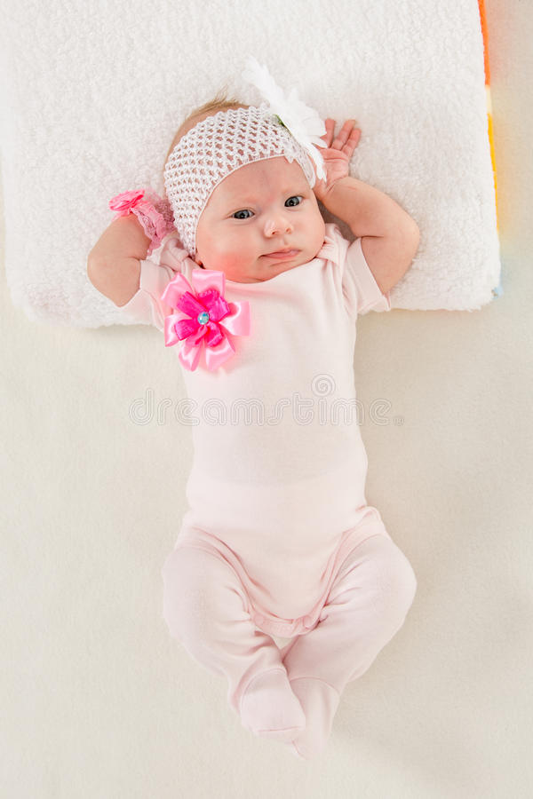 Baby girl lying in bed stretching. A two-month baby girl Europeans on the back with a bandage on his head with a flower lying on a soft bed royalty free stock images