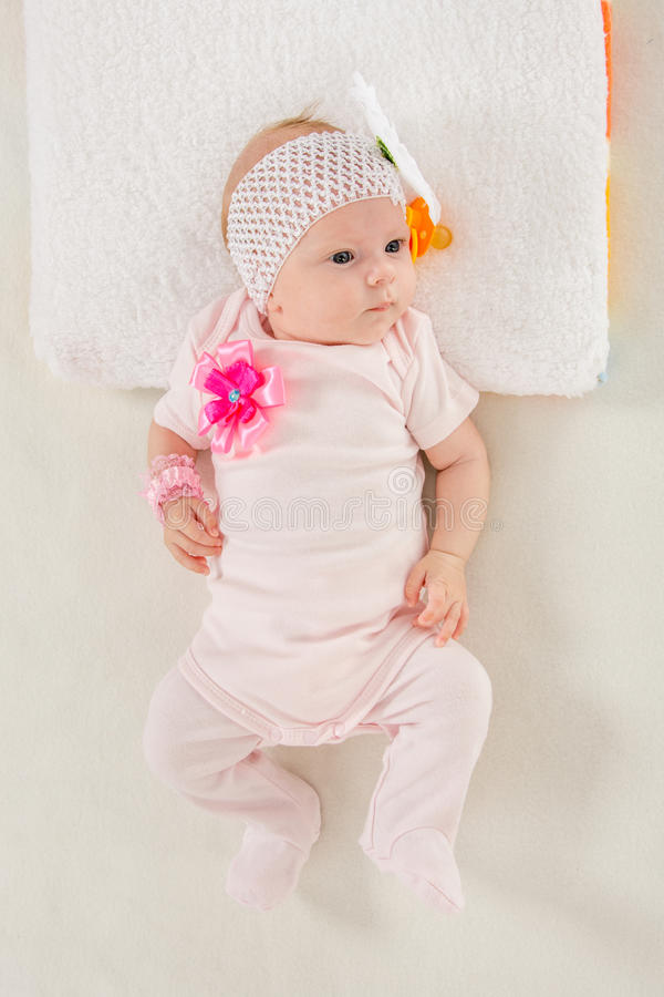 Baby girl lying in bed. A two-month baby girl Europeans on the back with a bandage on his head with a flower lying on a soft bed stock photos