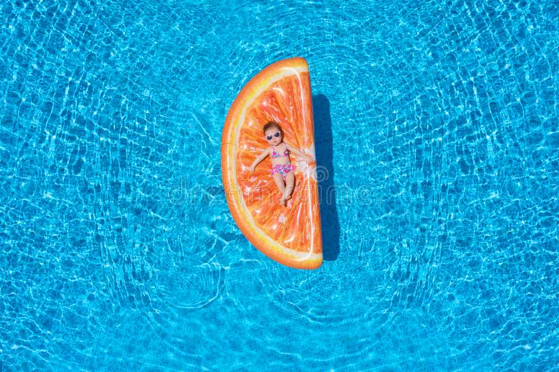 Baby girl is lying on a orange slice shaped float over blue pool water royalty free stock photos