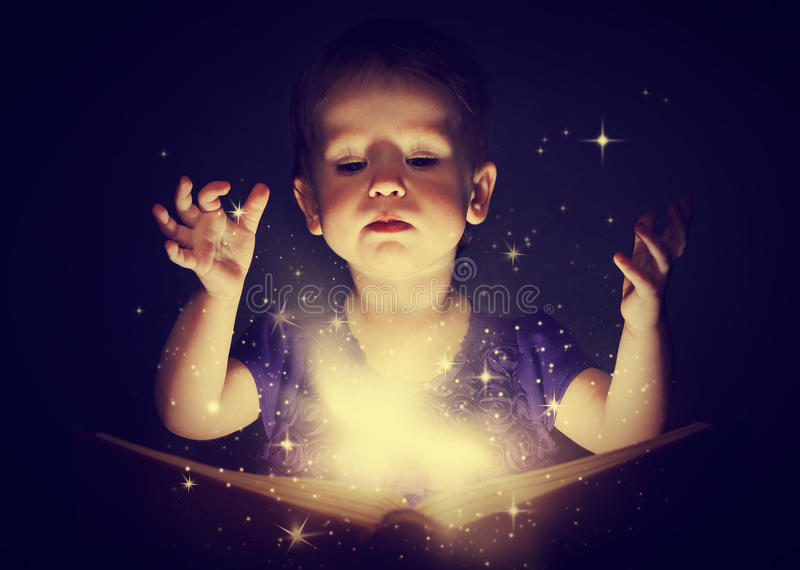 Baby girl with magic book. On a dark background royalty free stock photos