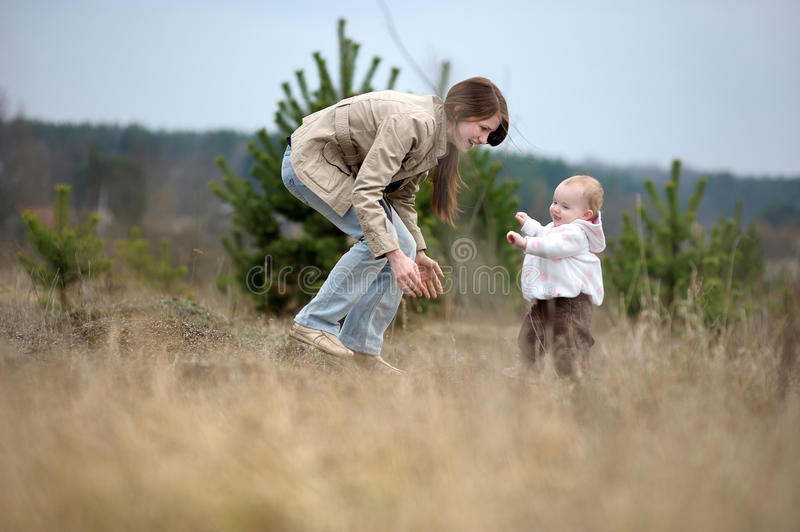 Baby girl making her first steps stock photo