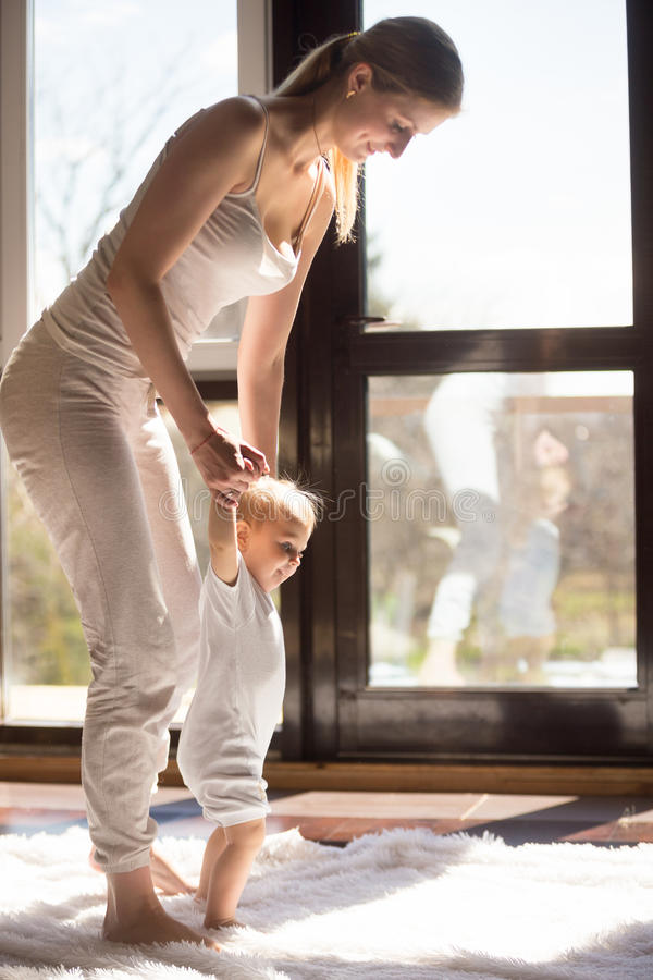 Baby girl making her first steps with mother at home royalty free stock photos