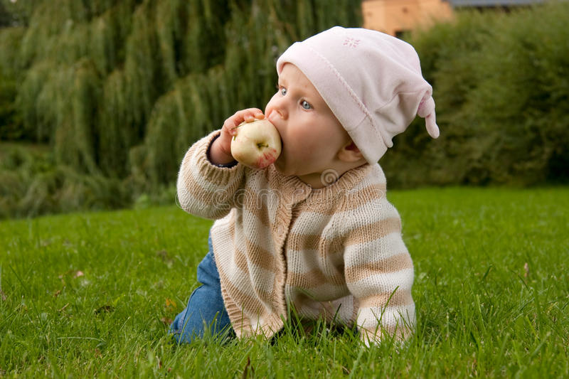 Baby girl in meadow royalty free stock photography