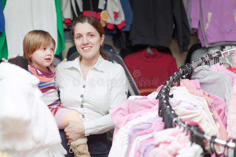 Baby girl with mother at clothes store. Baby girl with mother chooses wear at clothes store stock photography