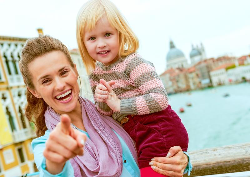 Baby girl and mother poiting in camera while standing on bridge stock photo