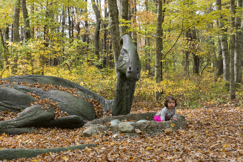 Baby Girl next to full size dinosaur. With beautiful foliage royalty free stock photos