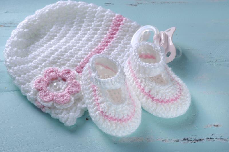 Baby girl nursery pink and white stripe wool booties and bonnet. Baby girl nursery pink and white stripe wool booties, bonnet and pacifier dummy on vintage aqua royalty free stock photos