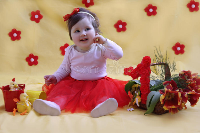 Baby girl one year anniversary. In red and yellow decor royalty free stock image