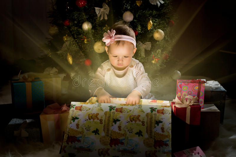 Baby girl. One-year-old little girl solemnize Christmas, sit under Christmas-tree and reach gift of box, horizontal photo stock photo