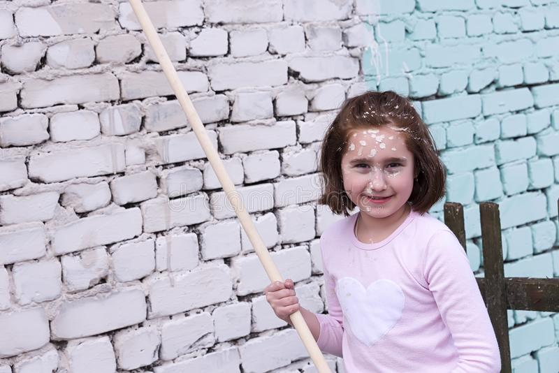 Baby girl paints the walls with roller and paint stock photography