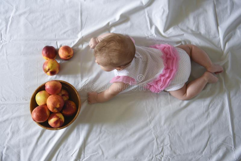 Baby girl with peaches royalty free stock photos