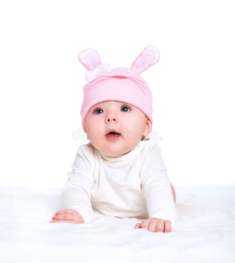 Baby girl in a pink hat with rabbit ears isolated on white. Cute baby girl in a pink hat with rabbit ears isolated on white background royalty free stock photos