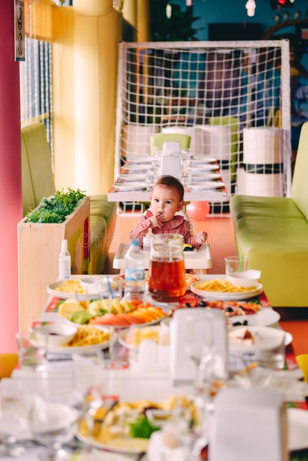 Baby girl in pink in highchair in front of big fest table at birthday party royalty free stock photo