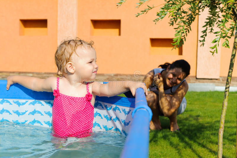 Baby girl in pink swimsuit. In the pool stock photography