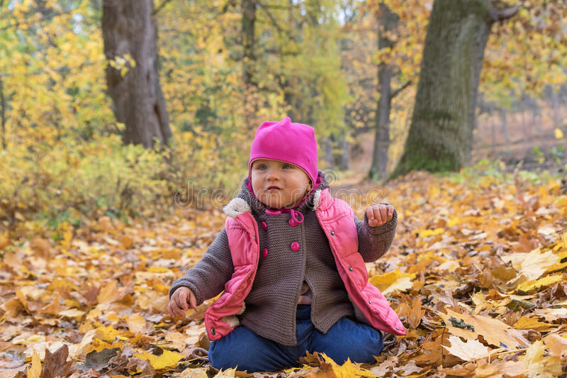 Baby girl in pink warm coat sitting on the ground royalty free stock image