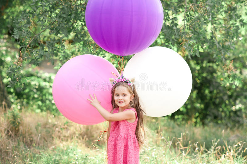 Baby girl playing with balloons stock photo