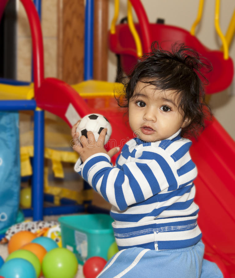 Baby Girl Playing with Balls in a Play Area stock image