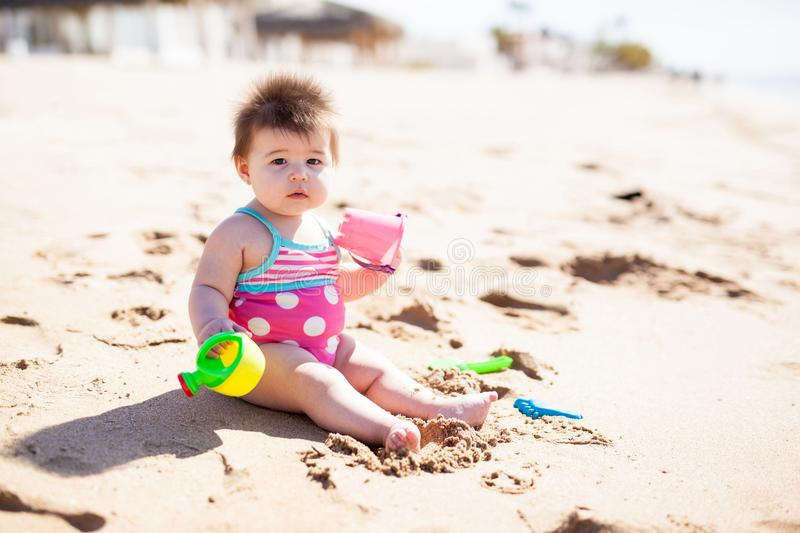Baby girl playing in the beach sand royalty free stock images