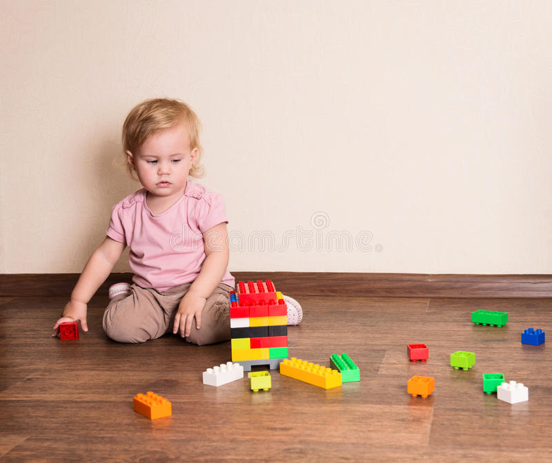 Baby girl playing with block toys at home or nursery royalty free stock image