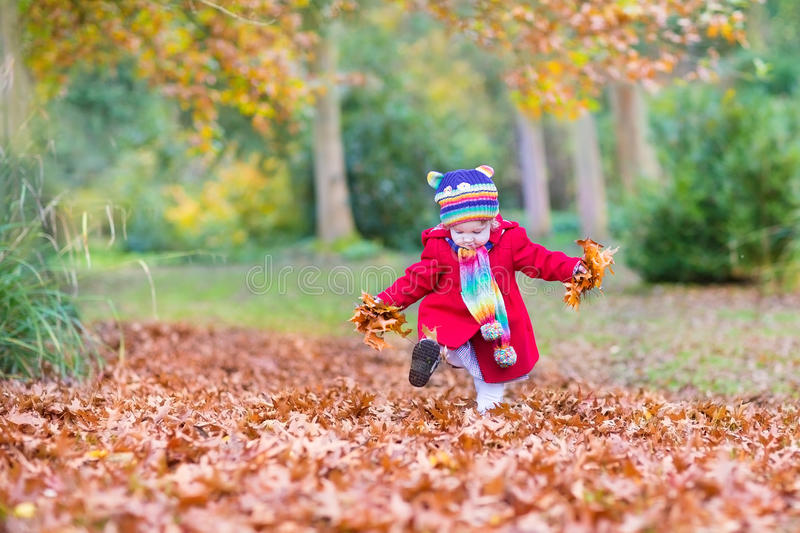 Baby Girl Playing With Golden Leaves In Autumn Park Stock Photo