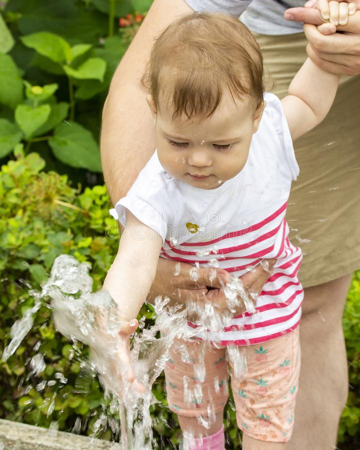 Baby girl playing with jets of water in a fountain. A child on a walk in the park plays with water, the baby climbs into the. Fountain Portrait of a child in royalty free stock photography
