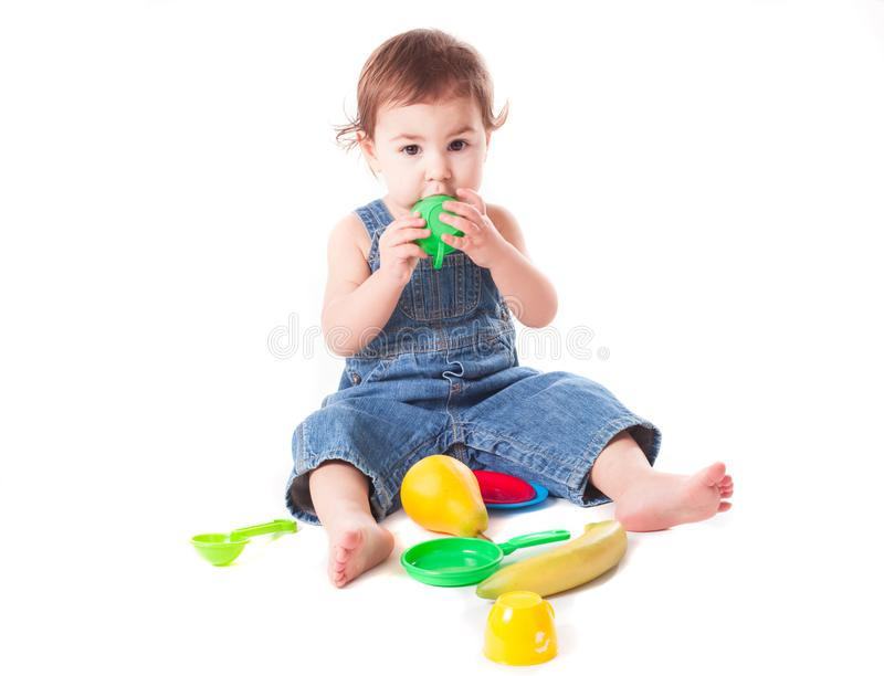 Baby girl playing with kitchen toys royalty free stock images