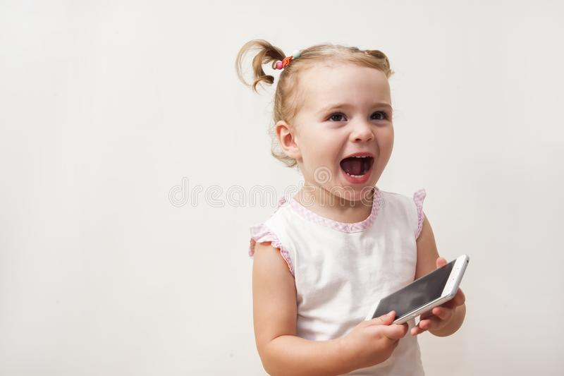 Baby girl playing with a mobile phone royalty free stock photo