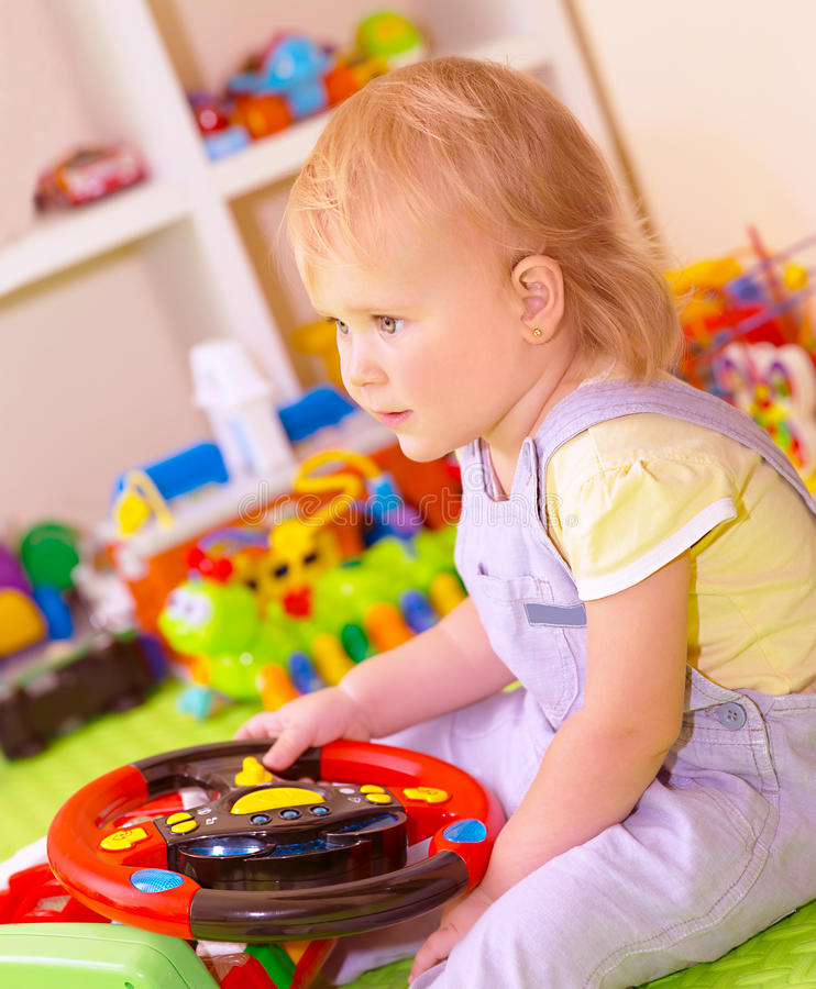 Baby girl in playing room. Portrait of cute little baby girl sitting in playing room, play with many colorful toys, spending time in daycare, elementary school royalty free stock photos