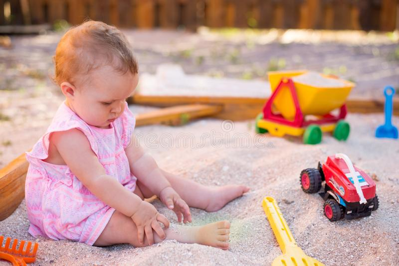 Baby girl playing in sandbox on outdoor playground. Child with colorful sand toys. Healthy active baby outdoors plays games stock photos
