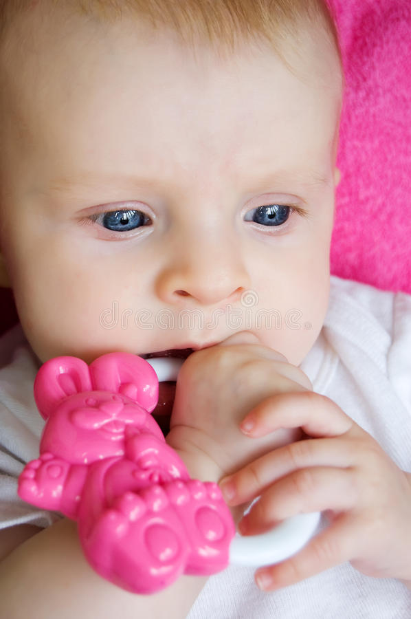 Baby girl playing with toy. Blue eyed baby girl playing with toy stock photos