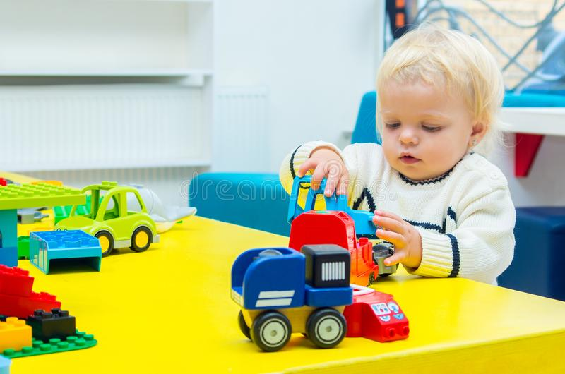 Baby girl playing toy cars. Little baby blond girl playing toy cars royalty free stock photo