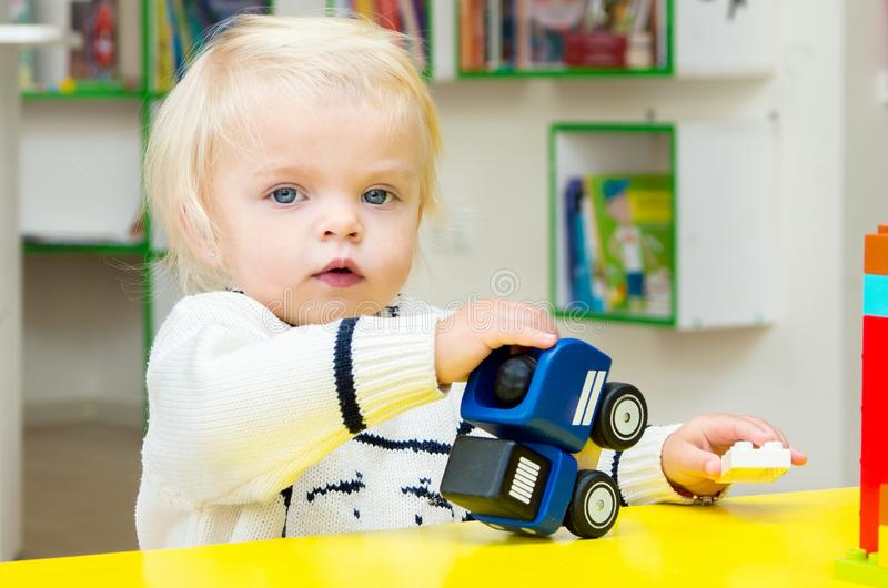 Baby girl playing toy cars. Little baby blond girl playing toy cars stock photography
