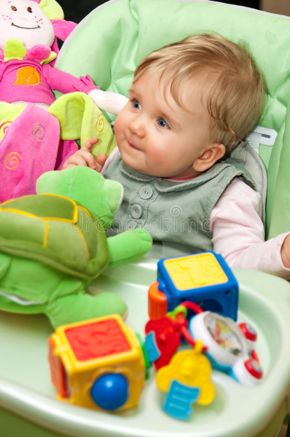 Baby girl playing with toys. Happy baby girl in high chair playing with toys stock photos