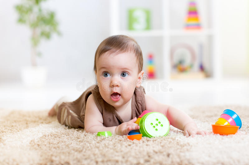 Baby girl playing with toys indoor stock photos