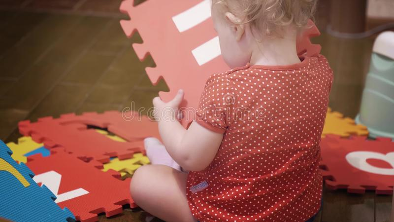 Baby girl plays with colorful puzzle carpet tiles with letters at home royalty free stock image