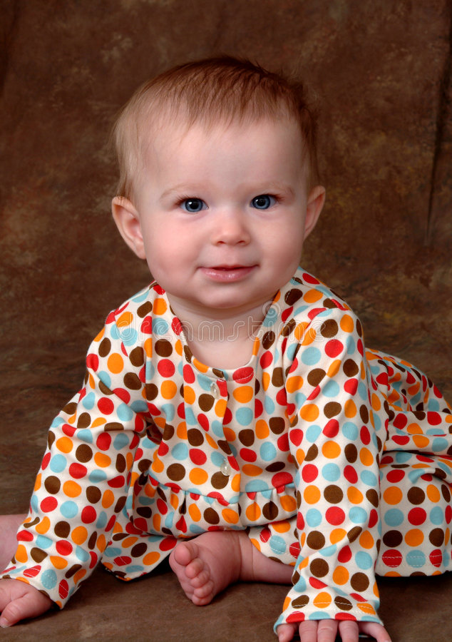 Baby Girl in Polka Dot Dress. Baby in sitting position, leaning forward to keep her balance, dressed in a polka dot dress stock photo