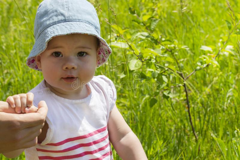 Baby girl portrait close-up, walk in nature, green meadow. Curious child. Girls in summer hat stock photo