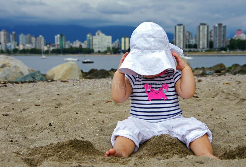 Baby girl pulling on sunhat, while sitting in sand at the beach. royalty free stock images