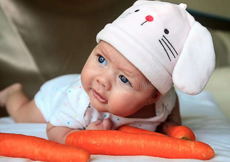 Baby girl in a rabbit hat. 2,5 month baby girl in a rabbit hat laying on her tummy. She is looking toward the camera and looks happy as now able to hold her head stock images