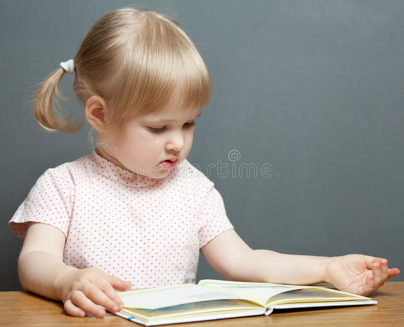 The baby girl is reading the book stock photos