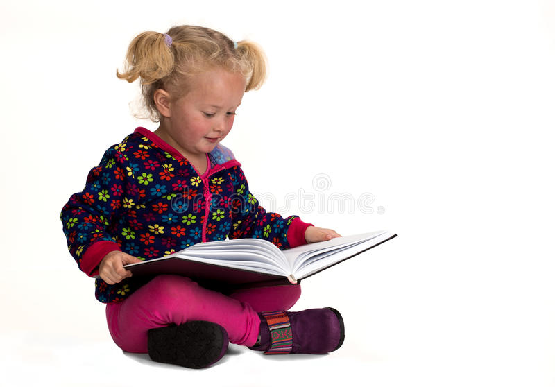 Baby girl reading stock photography