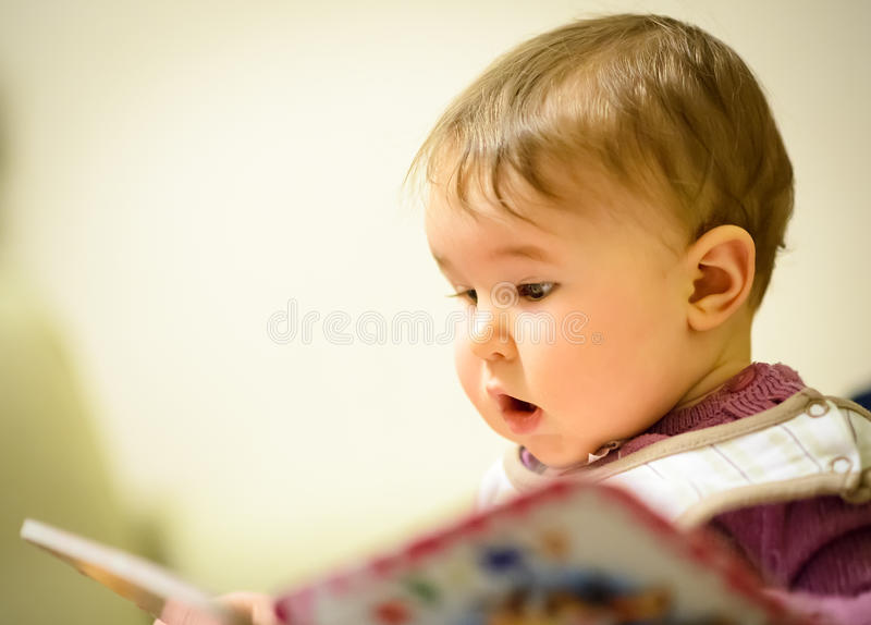 Baby girl reading a children's book royalty free stock photo