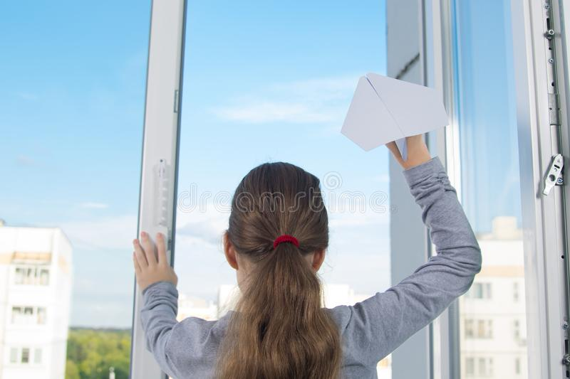 Baby girl, rear view, releases a paper plane from a plastic window, against the sky stock photos