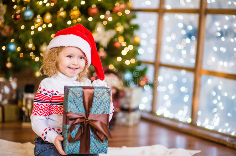 Baby girl in red santa hat holding big gift box near the Christmas tree royalty free stock photos