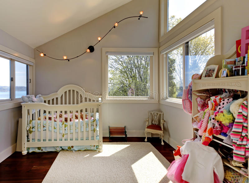 Baby girl room with white crib and clothes. stock photography