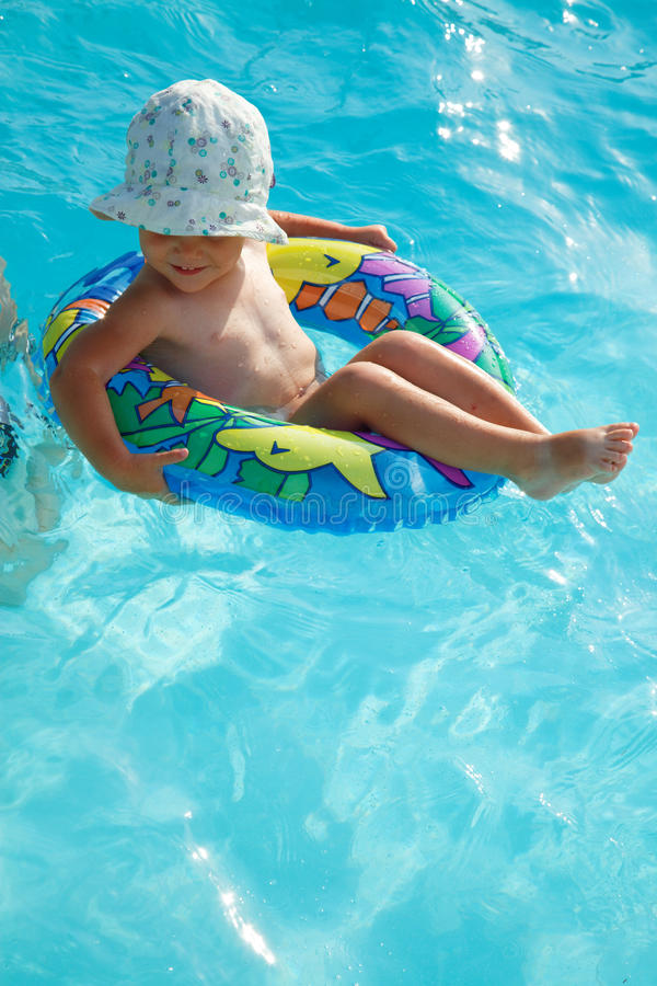 Baby girl in rubber ring. Floating in swimming pool with sun hat on her head royalty free stock photography