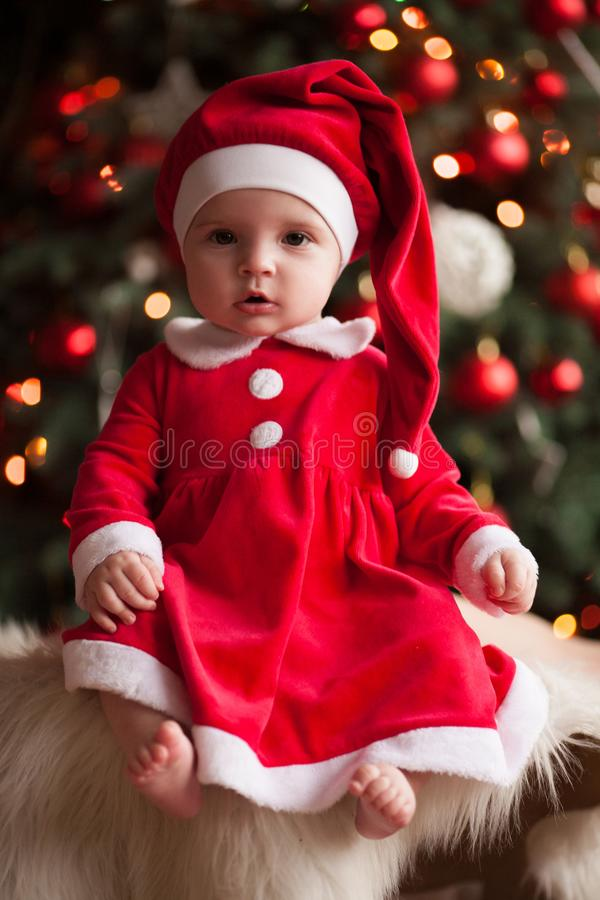 Baby girl in Santa Claus costume sits on fur rug against background of Christmas decorations. royalty free stock photo
